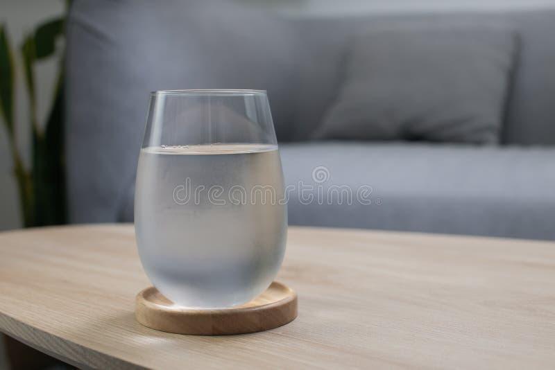 Szklanka bardzo zimnej wody na drewnianym stole w salonie zdjęcia stock