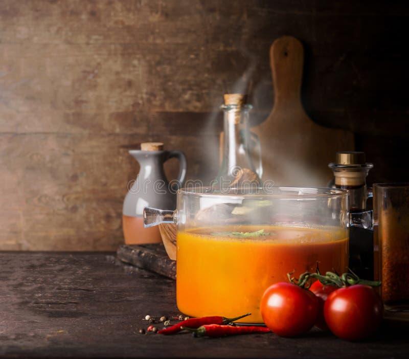 Szklany kucharstwo garnek z gorącą pomidorową polewką i cios z parowej pozycji na nieociosanym kuchennym stole z składnikami kosm obrazy royalty free
