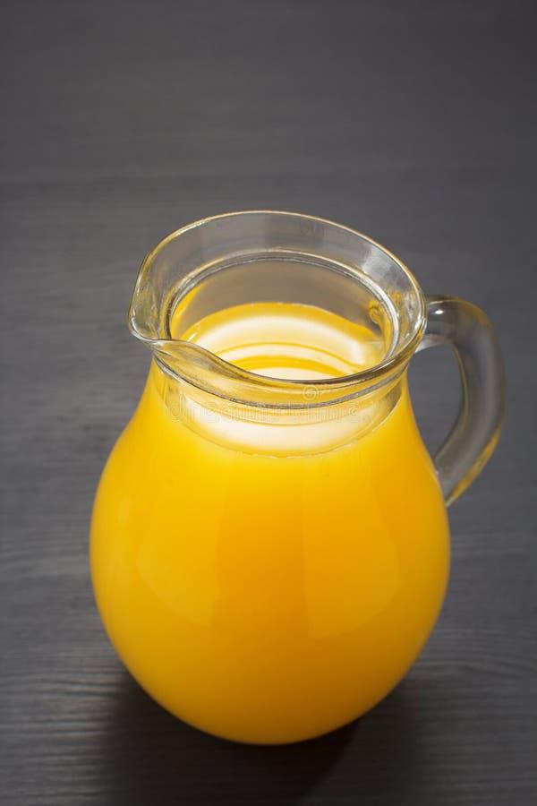 Szklany miotacz i sok pomarańczowy na drewnie fotografia stock