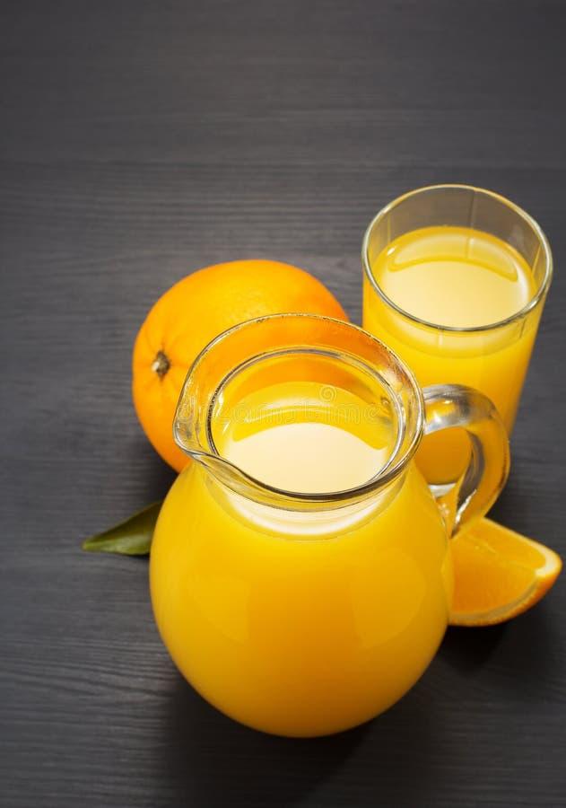 Szklany miotacz i sok pomarańczowy na drewnie zdjęcia stock