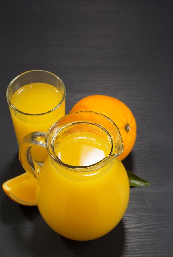 Szklany miotacz i sok pomarańczowy na drewnie obraz royalty free