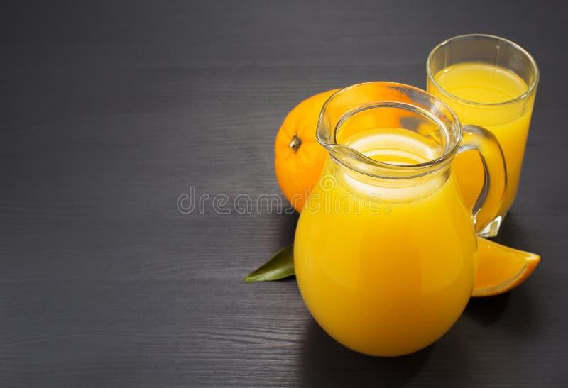 Szklany miotacz i sok pomarańczowy na drewnie obraz stock