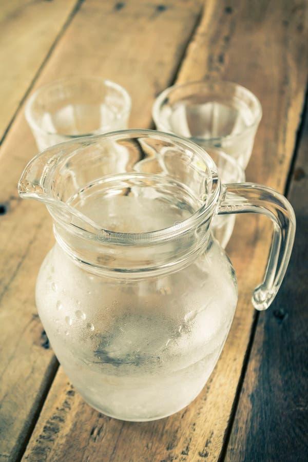 Szklany miotacz woda i szkło na drewnianym stole obraz stock