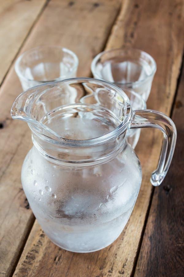 Szklany miotacz woda i szkło na drewnianym stole zdjęcia royalty free