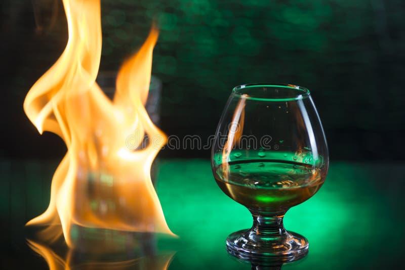 Szklany o whisky z lodem i wineglass koniak i ogień płonie na zielonym bokeh tle zdjęcie stock