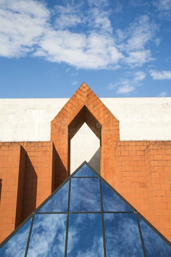 Szklany ostrosłup odbija niebo i chmury przed symetrycznym budynkiem zdjęcia stock