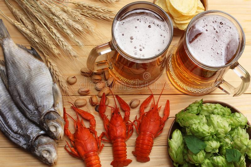 Szklany piwo z rakami, chmiel rożkami i pszenicznymi ucho na lekkim drewnianym tle, Piwny browaru pojęcie tła piwo zawiera gradie zdjęcia royalty free