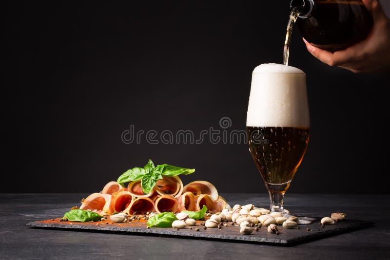 Szklany plombowanie z piwem, pistacjami i prosciutto, przyprawiał z czarnym pieprzem i basilem na ciemnym tle obraz royalty free