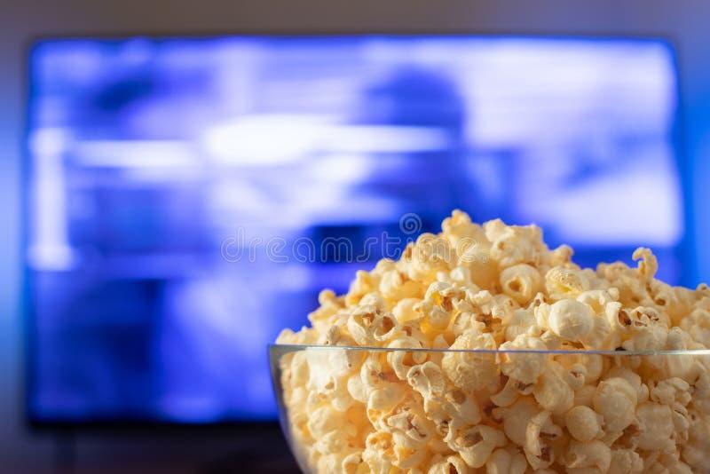 Szklany puchar popkorn i pilot do tv w tle TV pracuje Wieczór wygodny dopatrywanie film lub seriale telewizyjni przy obrazy royalty free
