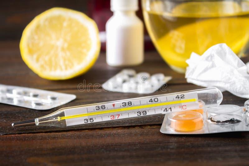 Szklany rtęć termometr z wysokotemperaturowym 37 5 przeciw tłu medycyny, cytryna, herbata, ludowi remedia, pastylki, obrazy royalty free