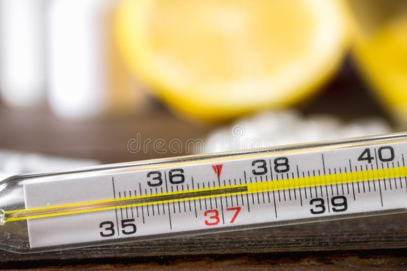 Szklany rtęć termometr z wysokotemperaturowym 37 5 przeciw tłu medycyny, cytryna, herbata, ludowi remedia, pastylki, zdjęcie stock