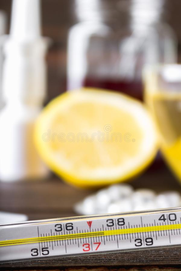 Szklany rtęć termometr z wysokotemperaturowym 37 5 przeciw tłu medycyny, cytryna, herbata, ludowi remedia, pastylki, fotografia royalty free