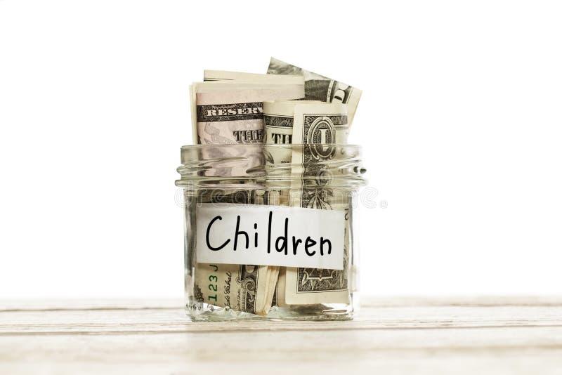 Szklany słój z pieniądze dla dzieci na drewnianym stole przeciw białemu tłu zdjęcie stock