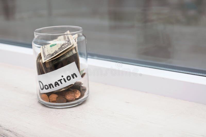 Szklany słój z pieniądze i etykietki darowizną na nadokiennym parapecie zdjęcie stock