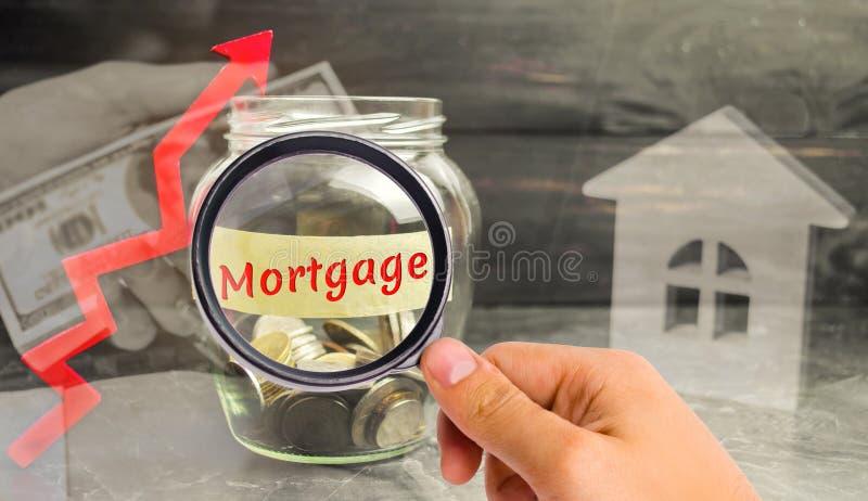 Szklany słój w górę strzały i z monetami i inskrypcją «hipoteka « Wzrost w stopach procentowych na hipotekach Hipoteczny pożyczan zdjęcie stock