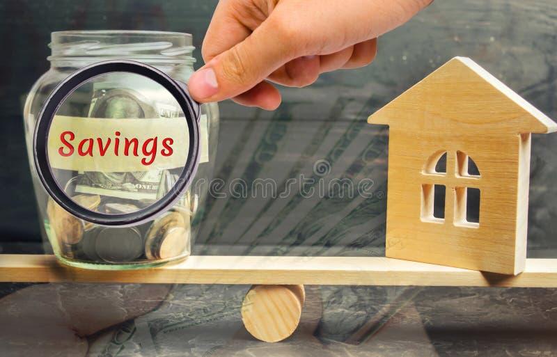 Szklany słój z, dom wpisowymi «i jesteśmy na skalach Pojęcie nieruchomość zakup zakupu dom zdjęcia royalty free