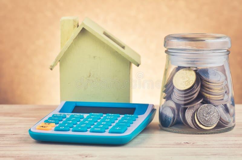 Szklany słój z monetami, kalkulatorem i domową repliką na drewnianym biurku dla kredytów mieszkaniowych, zdjęcie royalty free
