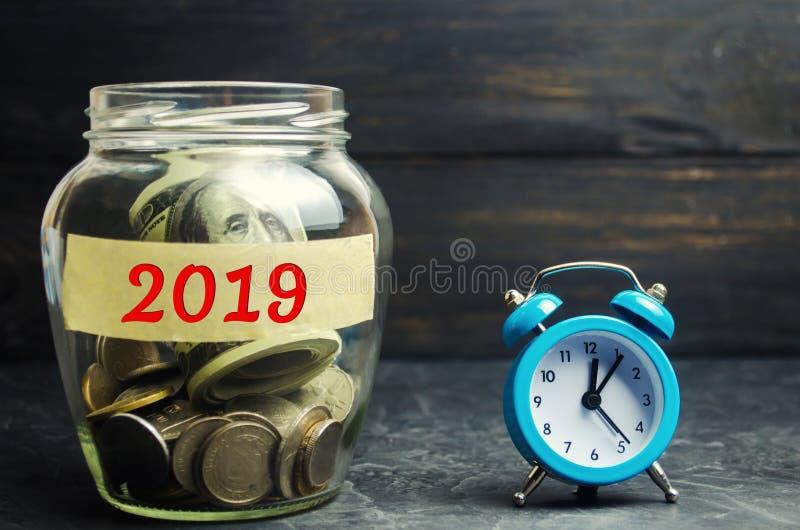 Szklany słój z monetami wpisowym ` 2019 ` i zegar Czas jest pieniądze Pieniężny budżeta planowanie Inwestycje i plany dla fotografia royalty free