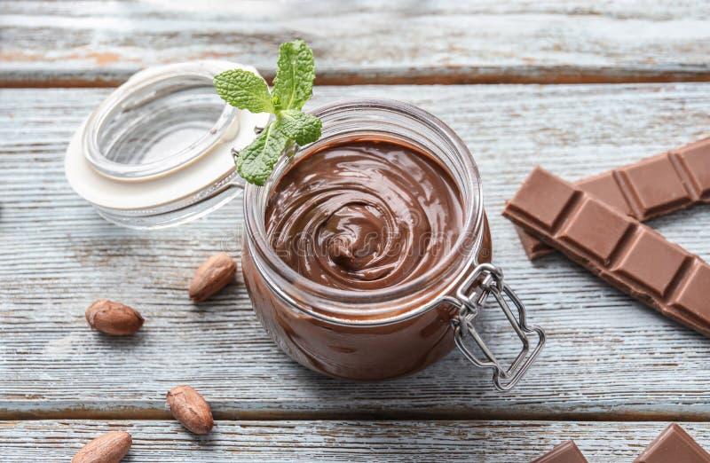 Szklany słój z smakowitą rozciekłą czekoladą na drewnianym stole fotografia royalty free