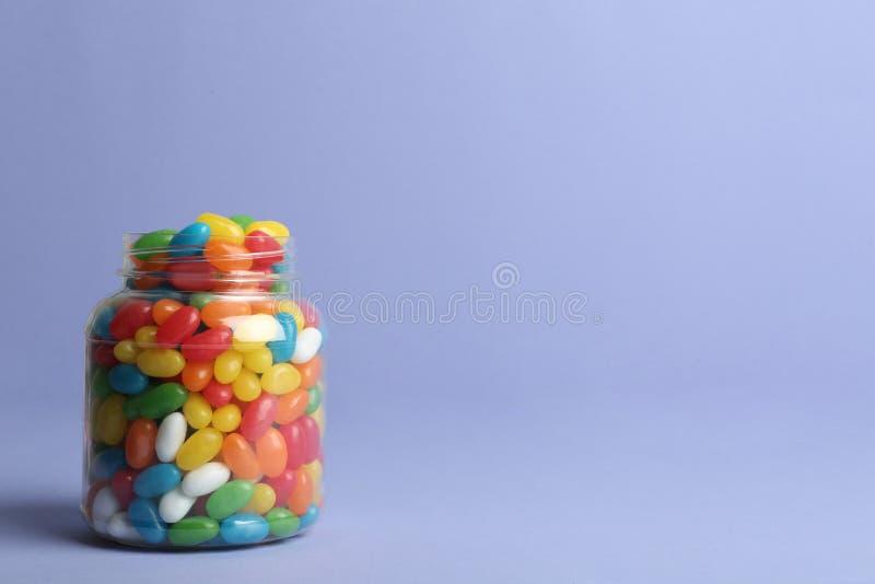 Szklany słój z wyśmienicie jaskrawymi galaretowymi fasolami na koloru tle zdjęcie stock