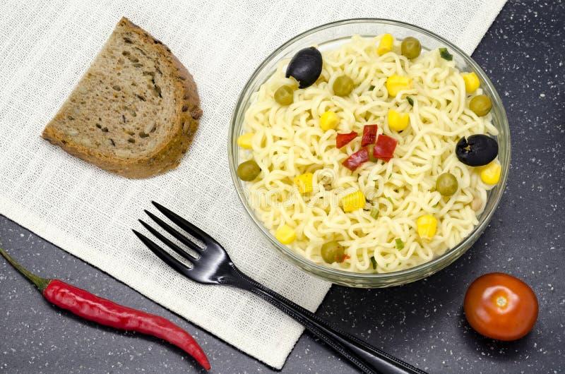 Szklany talerz kluski, rozwidlenie, chleb, czerwony pieprz i pomidor, zdjęcia royalty free