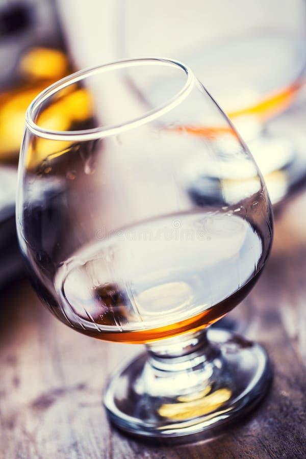 Szklany whisky koniaka brandy lub rum Jedna druga folował szkła koniak na drewnianej powierzchni zdjęcie stock