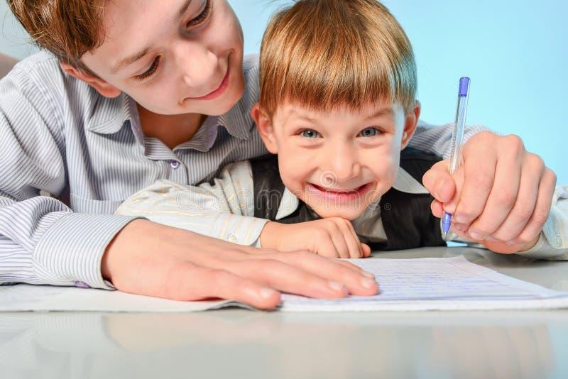 Szkoła średnia uczeń przygotowywa pierwszy równiarki w pisać i przygotowywać dla szkoły Stary brat uczy młodego obraz royalty free