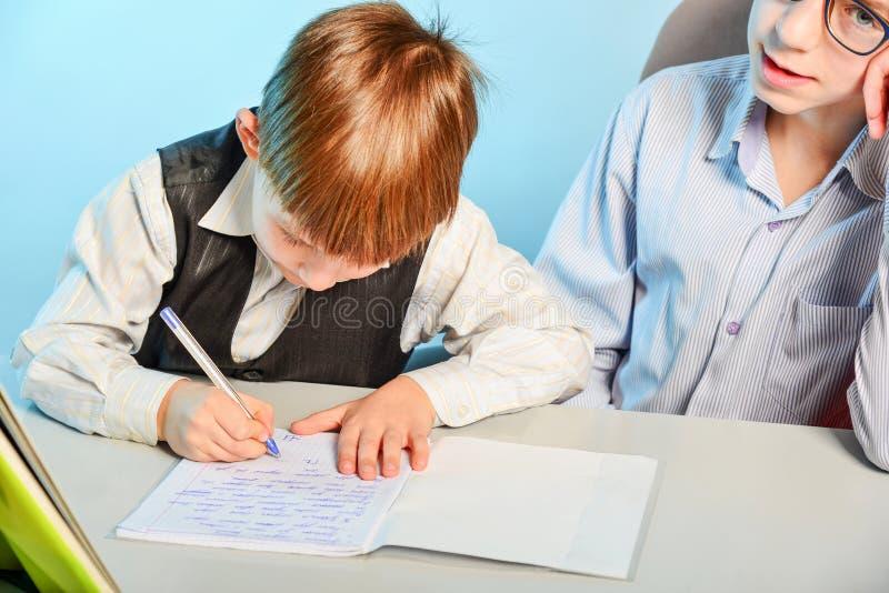 Szkoła średnia uczeń przygotowywa pierwszy równiarki w pisać i przygotowywać dla szkoły Stary brat uczy młodego zdjęcia stock