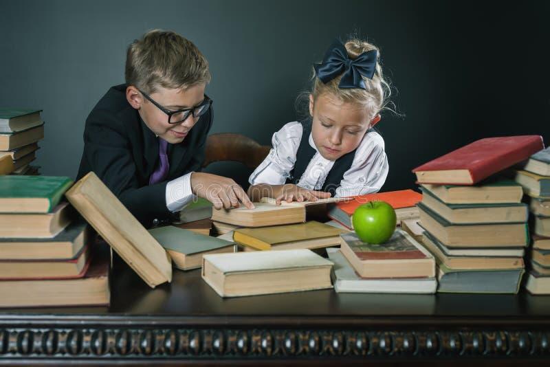 Szkoła żartuje czytać książkę przy biblioteką obraz stock