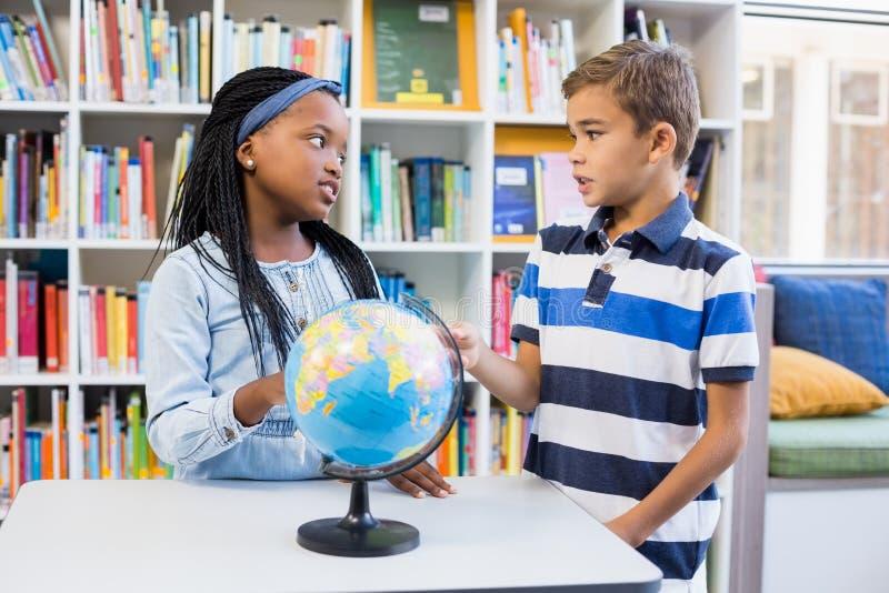 Szkoła żartuje dyskutować z each inny w bibliotece z kulą ziemską na stole obrazy stock