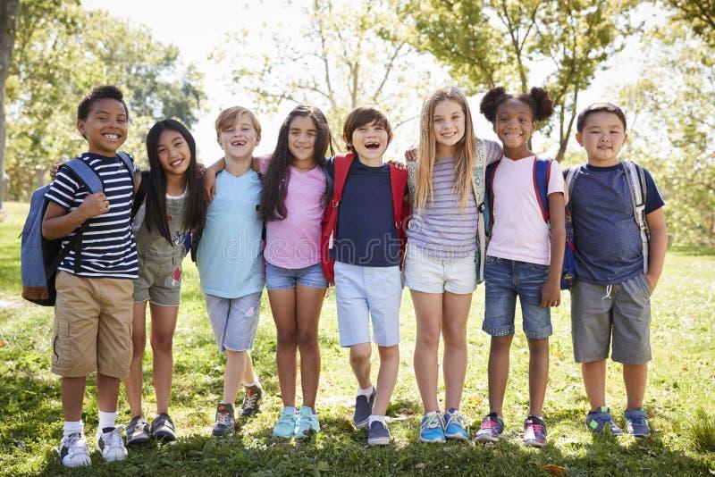 Szkoła dzieciaki stoją obejmować z rzędu outdoors, pełna długość zdjęcie royalty free