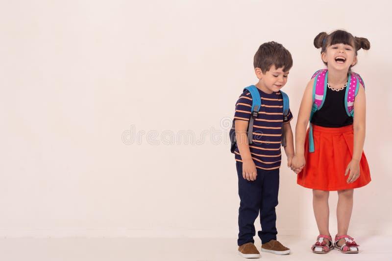Szkoła dzieciaki trzyma białą pustego miejsca lub bielu kartę z plecakami zdjęcie stock