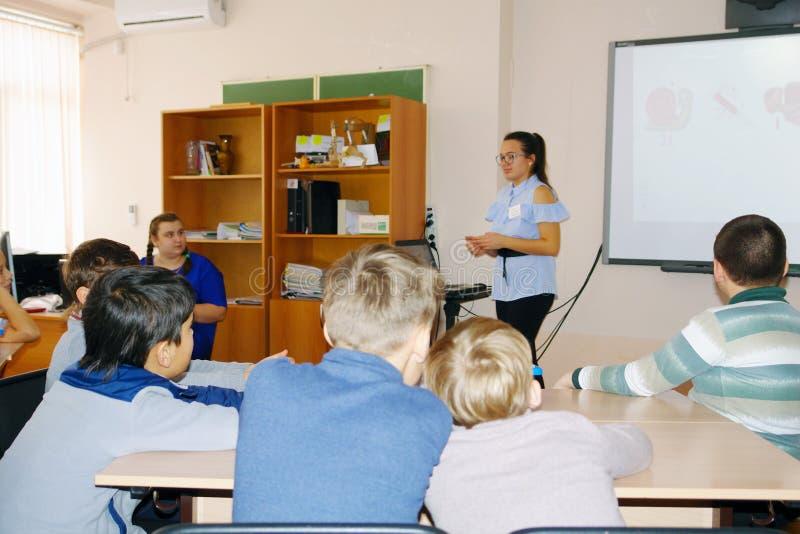 Szkoła dzieciaki w klasie z nauczyciel kobietą obrazy stock