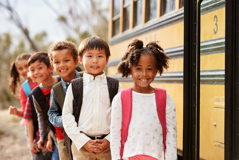 Szkoła podstawowa żartuje stać w kolejce dostawać dalej autobus szkolny zdjęcia stock