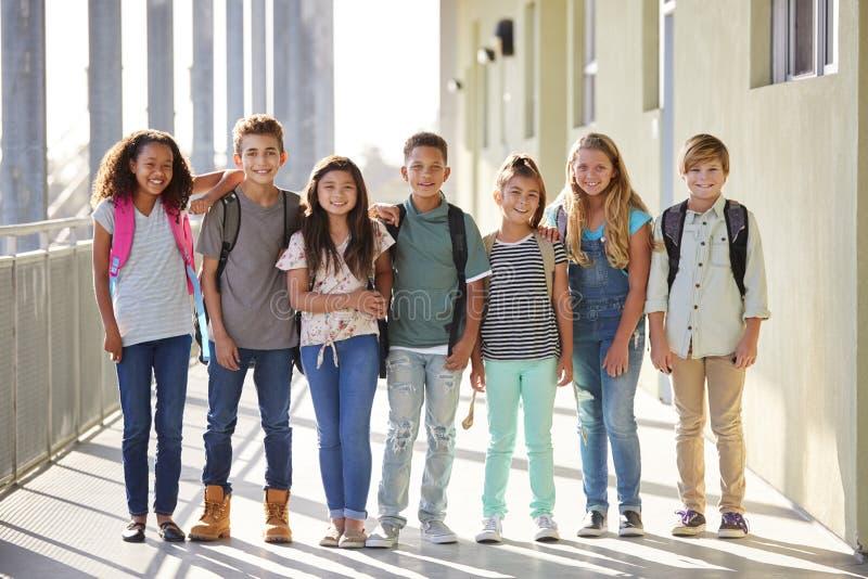 Szkoła podstawowa dzieciaków stojak w korytarzu patrzeje kamerę obraz royalty free
