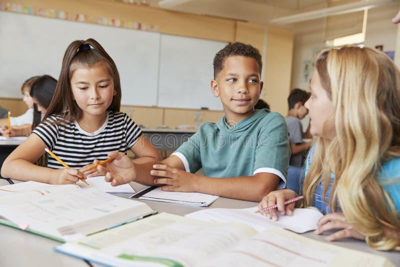 Szkoła podstawowa dzieciaki w klasowym działaniu wpólnie przy biurkiem zdjęcia stock