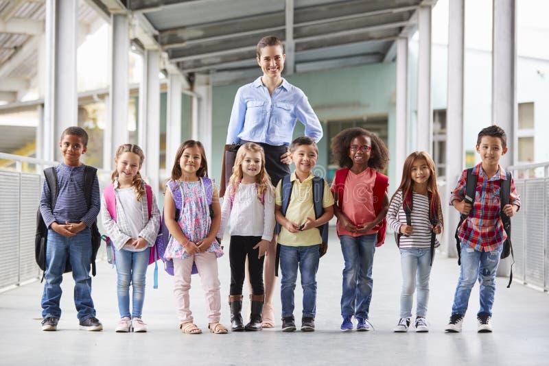 Szkoła podstawowa nauczyciel i jej ucznie w szkolnym korytarzu fotografia stock