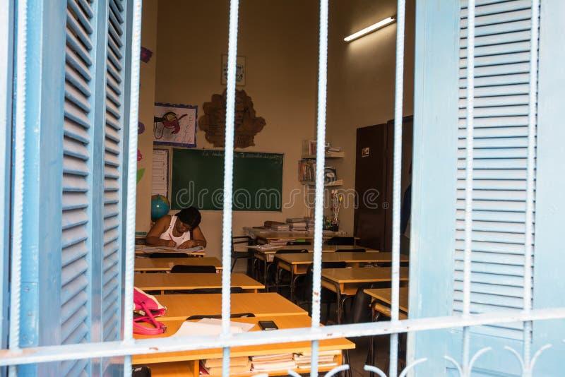Szkoła podstawowa nauczyciel koryguje pracę domową wśród puści clas fotografia stock