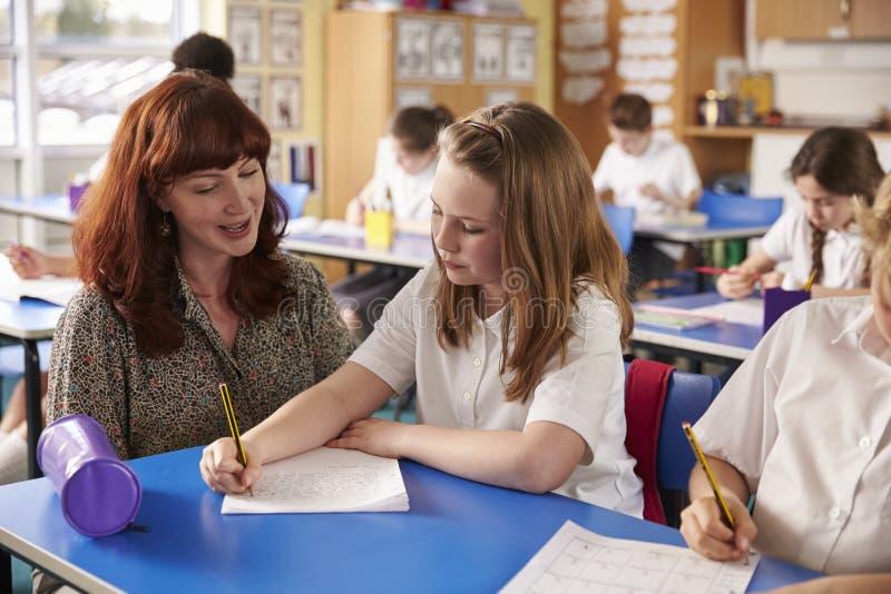 Szkoła podstawowa nauczyciel pomaga dziewczyny writing przy jej biurkiem obrazy royalty free