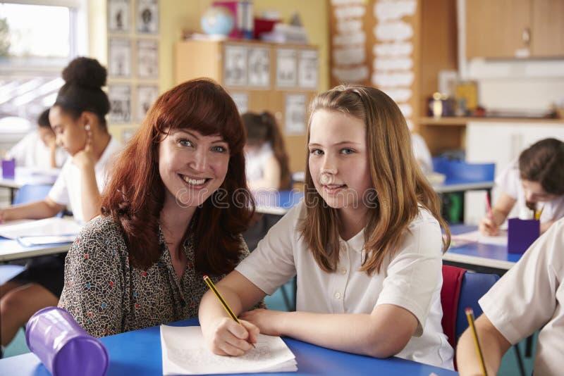 Szkoła podstawowa nauczyciel z dziewczyną przy jej biurka spojrzeniem kamera zdjęcia stock