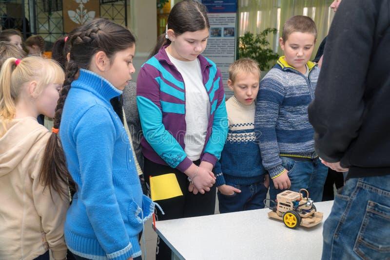 Szkoła podstawowa ucznie patrzeje domowej roboty samochód modelują obraz royalty free