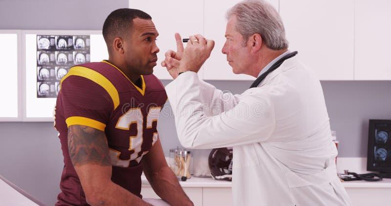 Szkoła wyższa gracz futbolu ma senior lekarki przegląd jego concussi zdjęcia stock