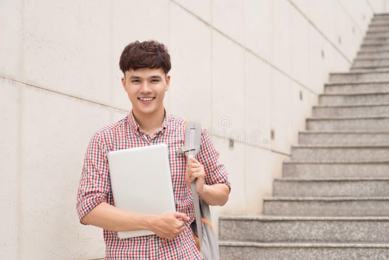 Szkoła wyższa męskiego ucznia mienia azjatykci laptop w kampusie fotografia stock