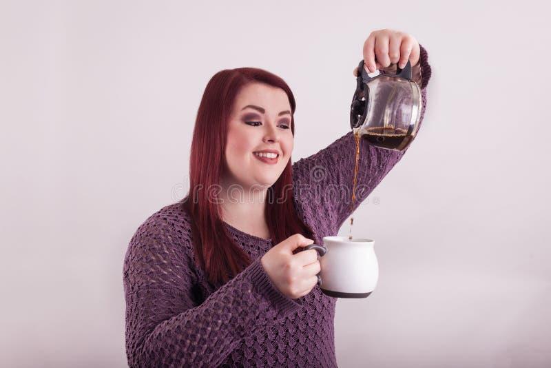 Szkoła wyższa starzał się studenckiego dolewania gorącą kawę od karafki w filiżankę obraz royalty free