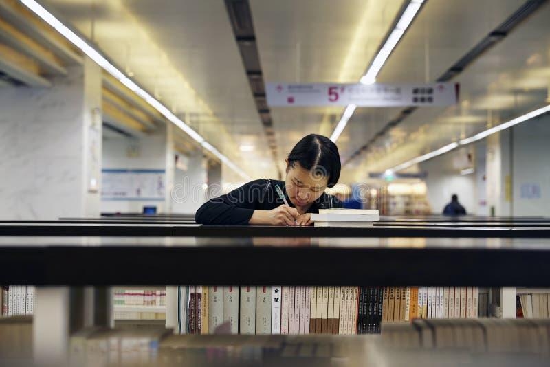 Szkoły średniej dziewczyny writing w bibliotece i czytanie zdjęcie royalty free