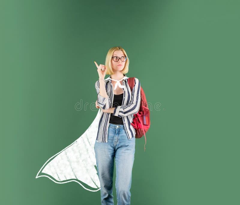 Szkoły średniej pojęcie - copyspace Śmieszny uczeń w szkłach nad chalkboard tłem Śmieszny żeński młody nauczyciel w zdjęcia stock