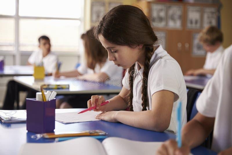 Szkoły podstawowej dziewczyna pracuje przy jej biurkiem w klasie zdjęcia stock
