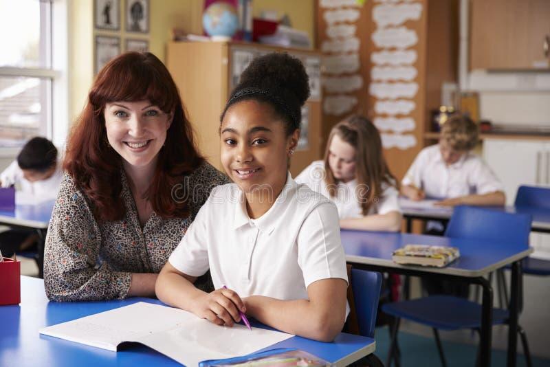 Szkoły podstawowej dziewczyna w klasowy patrzeć kamera i nauczyciel obrazy stock