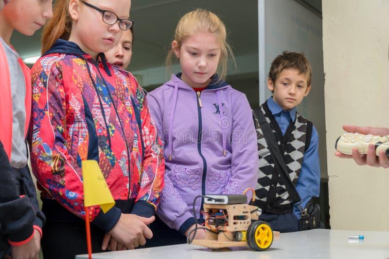 Szko?a podstawowa ucznie patrzeje domowej roboty samoch?d modeluj? obrazy stock