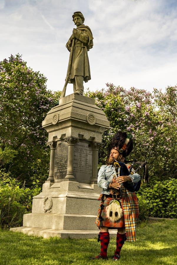 Szkocki bagpiper ubierał w tradycyjnej czerwieni i czerni tartanu sukni obraz stock